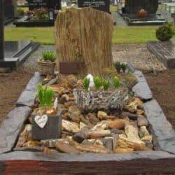 Grafsteen van versteend hout met een omranding van leisteen